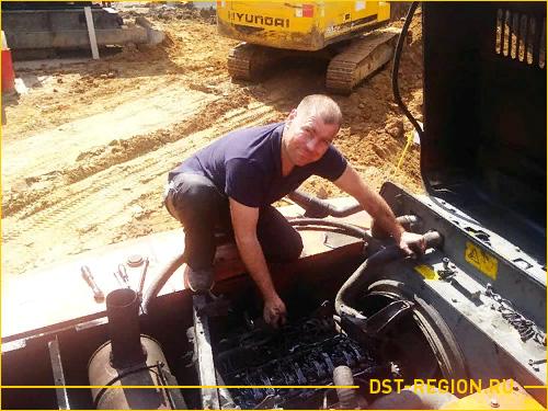 Мастер проводит диагностику двигателя экскаватора